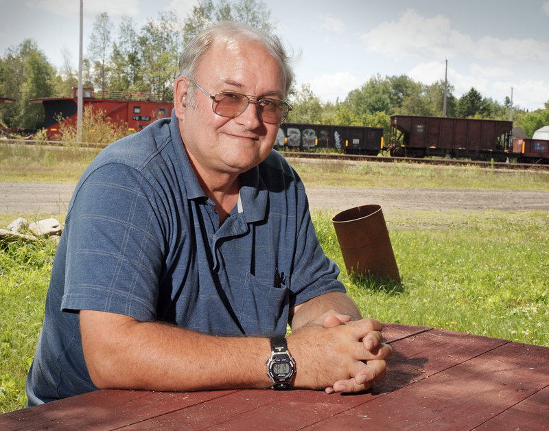 """Stephen Dean, pastor at the United Methodist Church, lives next to the rail yard at Brownville Junction in Brownville, which he says was a """"hopping place"""" when he was a boy growing up here."""