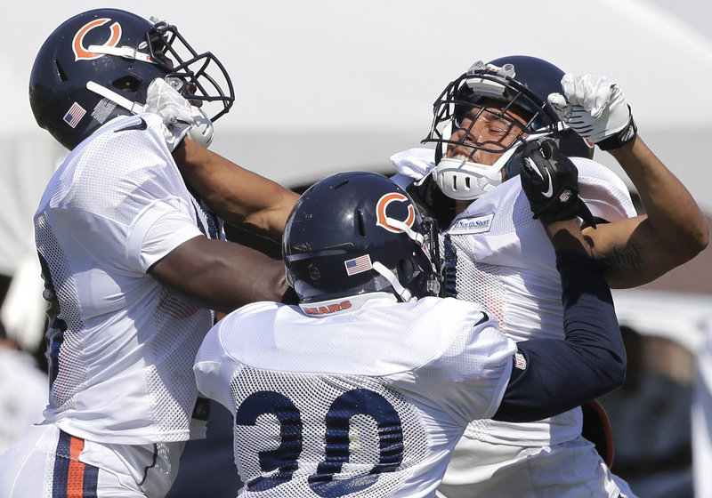 Isaiah Frey, right, a cornerback, works with Zackary Bowman, left, and Demontre Hurst as the Chicago Bears went through drills Thursday during training camp at Bourbonnais, Ill.