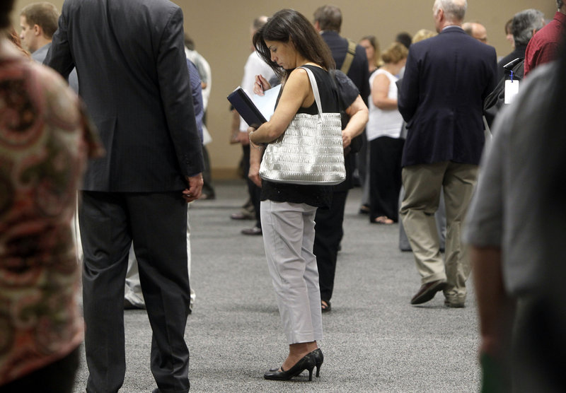 In this July 15 photo, a woman waits to talk with employers at a job fair for laid-off IBM workers in South Burlington, Vt. The Labor Department said Friday that U.S. employers added 162,000 jobs in July, the smallest gain since March.