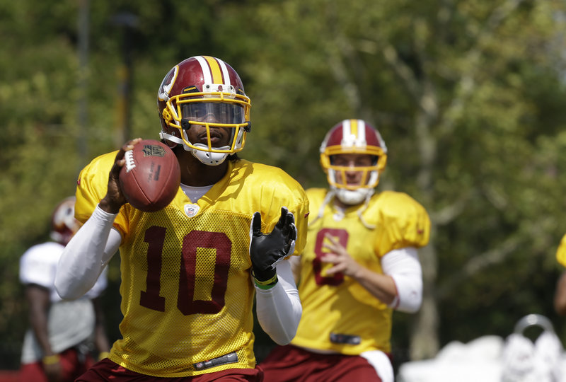 Robert Griffin III looks for a receiver Friday while working out with the Washington Redskins during an afternoon session at training camp in Richmond, Va.