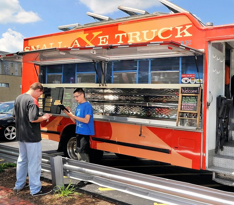 Because the Small Axe Truck is over the city's 20-foot size limit, it must serve its meals from a private parking lot on Congress Street.