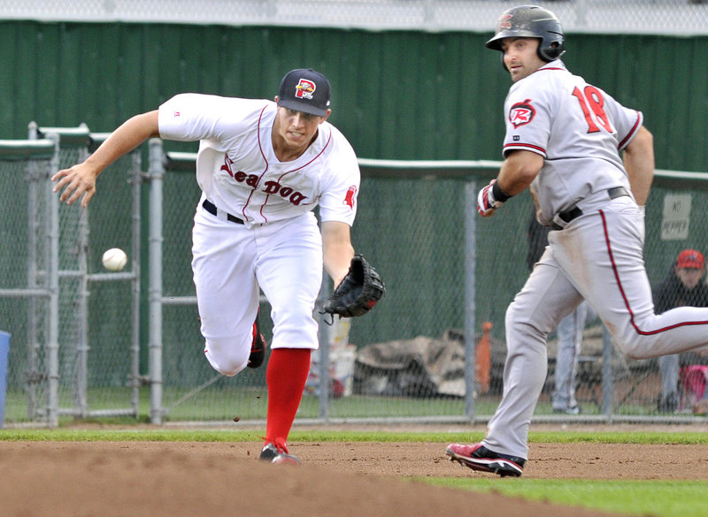 Third baseman Garin Cecchini of the Portland Sea Dogs moves in to collect a grounder in front of Tyler LaTorre of Richmond.