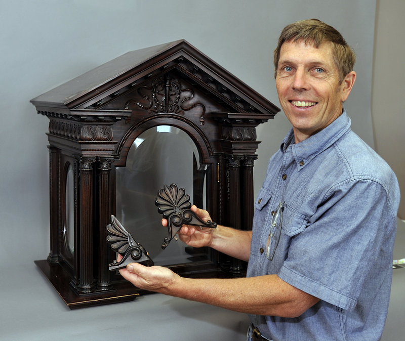 Jon Brandon shows two pieces of an 1898 clock bonnett to be repaired by his company.