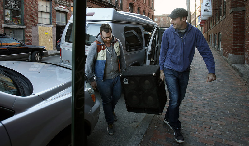 Bandmates Matt Cosby and Pete Kilpatrick lug equipment into the Market Street venue before the show. These days, musicians often struggle to be heard above all the competition.