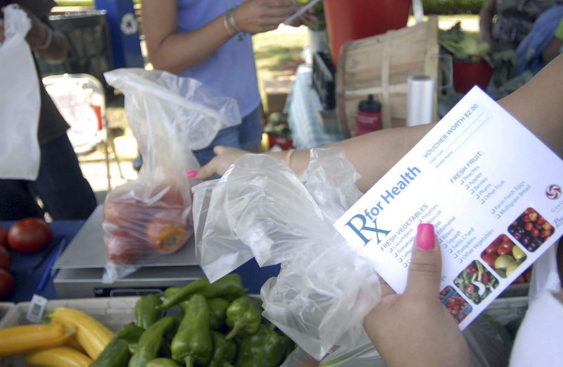 """Nely Pagan of Norwich, Conn., uses vouchers from the William W. Backus Hospital to buy vegetables at the farmers market in downtown Norwich. """"It's very helpful,"""" she said. 'We have a lot of fruit and vegetables at home."""""""