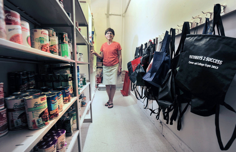 Portland High School assistant principal Kathie Marquis-Girard stands in the school's food pantry, which provides food items for students in need. The backpacks on the right allow the students to carry the food items without attracting undue attention.