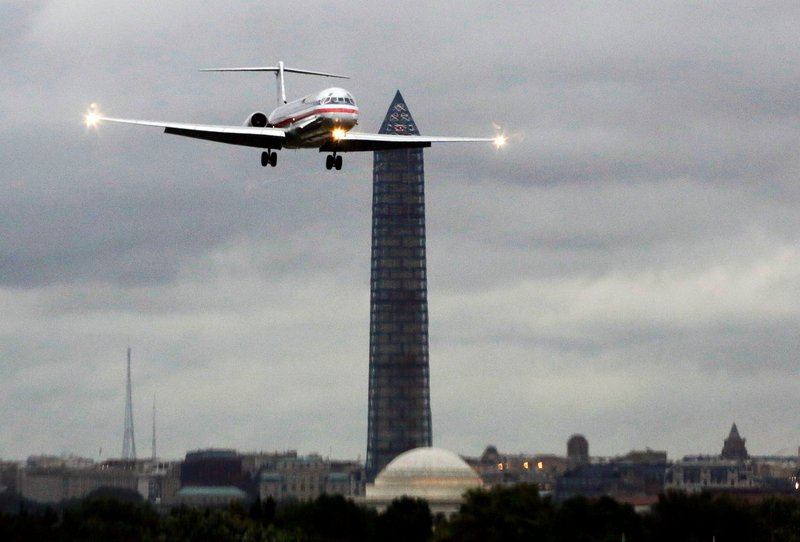 An American Airlines jet passes the Washington Monument as it lands at Ronald Reagan National Airport, in Washington, D.C. American and US Airways say that a merger between them would eliminate the service gaps and weaknesses they have as individual airlines.