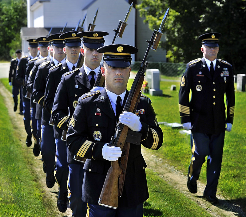 Members of the Maine Military Funeral Honors Program, part of the Maine National Guard, enter the Pleasant Ridge Cemetery in Hiram on Thursday to honor four servicemen from the same family killed in past wars.