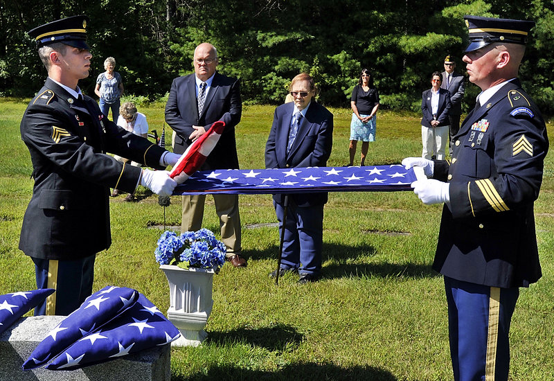 As family look on, Sgt. Casey Lawrence, left, and Sgt. David Chabe, fold the flag during a special ceremonial service in Hiram for four servicemen with the Lyons and Gray families killed in past wars.