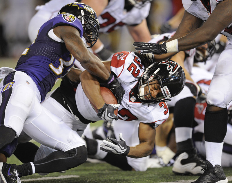Jacquizz Rodgers of the Atlanta Falcons rolls into the end zone Thursday night as James Ihedigbo of Baltimore goes for the ball during the Ravens' 27-23 victory in an exhibition game.
