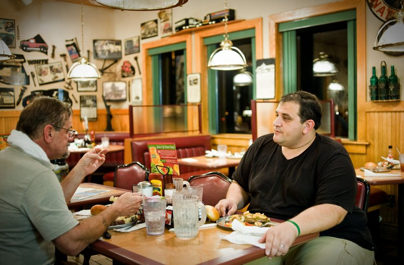 David Ryser, left, and son Charles Ryser of Forsyth, Ga., eat after showering at a truck stop recently in Bordentown, N.J. The Rysers oppose the federal rules to counter fatigue.