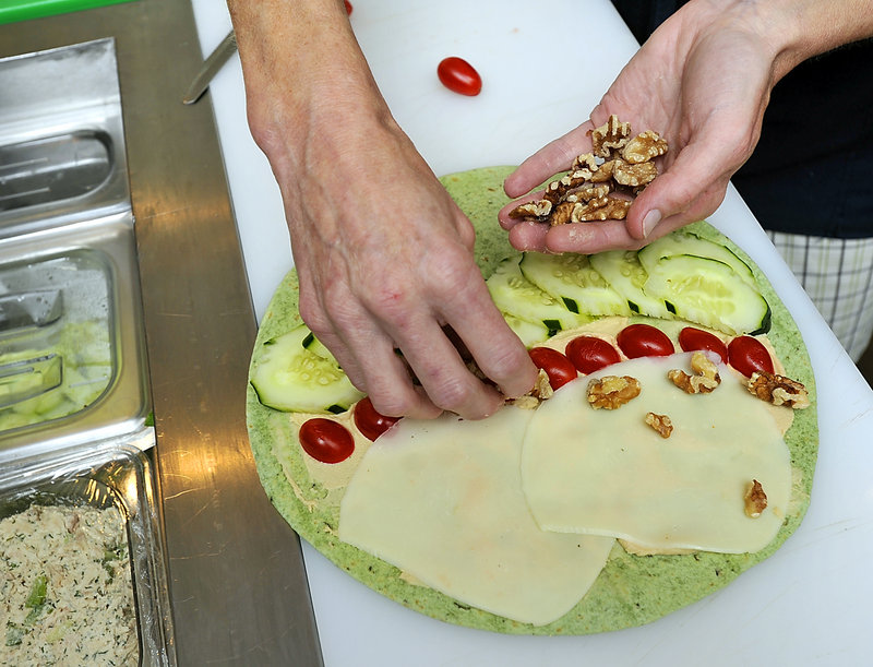 Jeannie Dunnigan, owner of Cia Cafe in South Portland, makes a veggie roll-up with fresh local produce.
