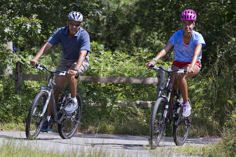 """President Obama and his daughter Malia, 15, ride bikes Friday in Manuel F. Correllus State Forest in West Tisbury, Mass. First lady Michelle Obama, with daughter Sasha, 12, passed ahead of them during their family vacation on Martha's Vineyard. The president said he's having a """"great time as always"""" on the island. He returns to work Sunday."""