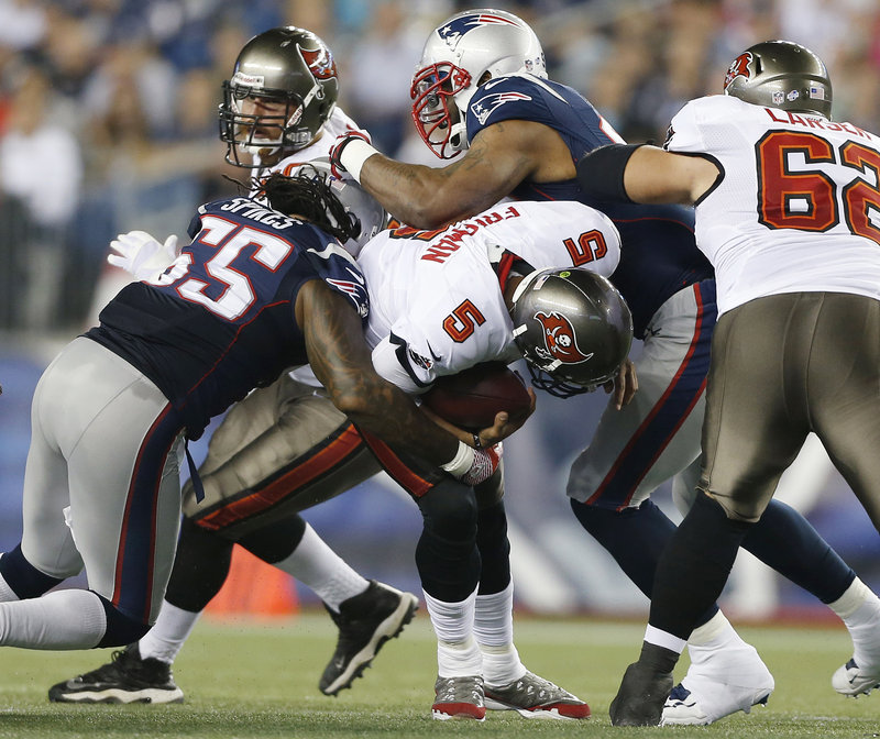 New England middle linebacker Brandon Spikes, left, and defensive tackle Tommy Kelly sack Tampa Bay Buccaneers quarterback Josh Freeman during the first quarter.