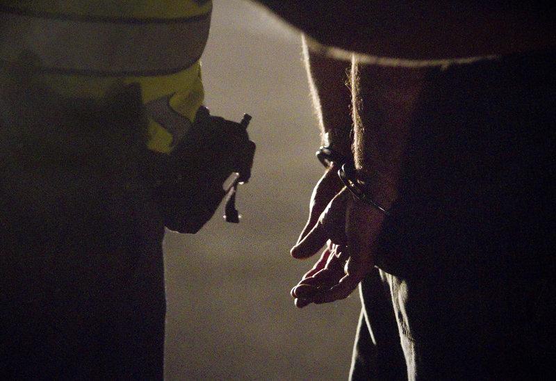 Police cuff a drunken driving suspect.