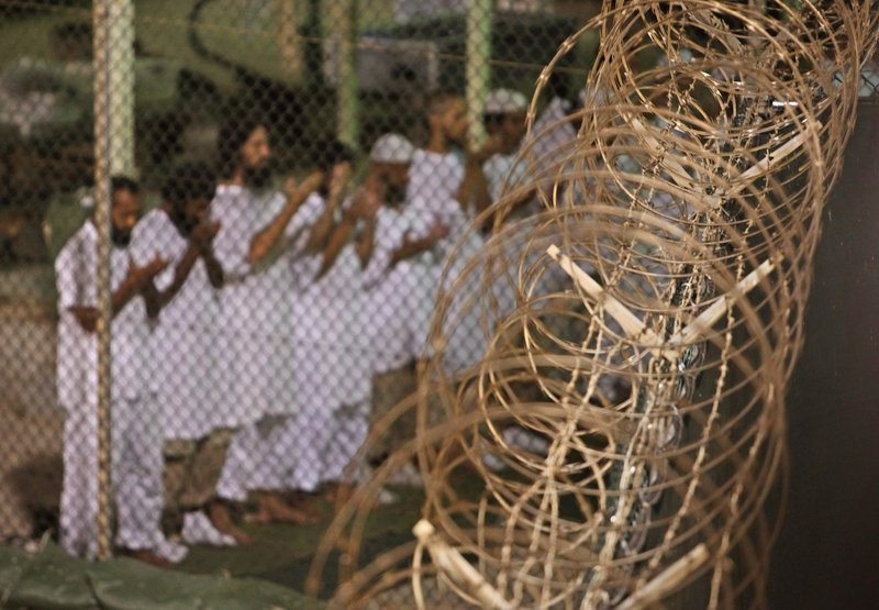 Guantanamo detainees pray before dawn near a fence of razor-wire at the prison on the U.S. naval base in Cuba. The prison once held as many as 680 men but now has 166 prisoners as the government figures out how to close the facility.