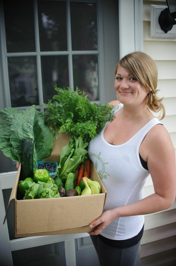 Casco Bay Organics owner Jillian Hilton delivers a small box of fresh produce to a home in Portland.