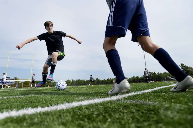 Falmouth boys' soccer player Nick Buckley works on a dribbling move as he tries to maneuver past a teammate during the team's first practice.