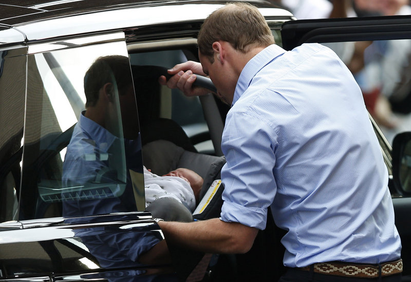 Prince William slides his son's car seat into the back of a four-wheel drive vehicle outside a London hospital on July 23.