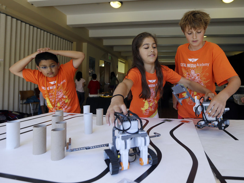 Saci Marty, center, and Callum Brown, right, put their robotic Lego Mindstorms units through an obstacle course during a Digital Media Academy workshop, in Stanford, Calif.
