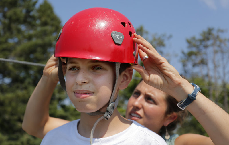 Salar Salim, 12, of Portland, originally from Iraq, gets some help from Ayla Zeimer getting his helmet on right for the zip line.