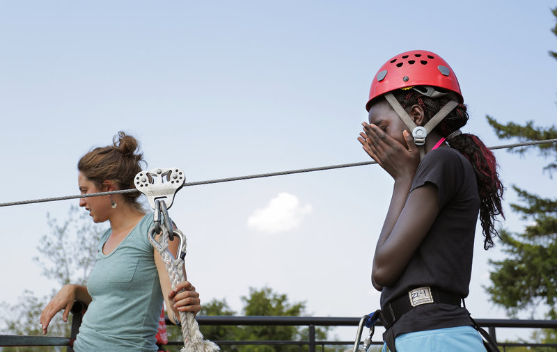 Doki Yanga, 12, of Portland deals with her nervousness Thursday as she prepares to ride the zip line on Cow Island during a five-day confidence-building experience.