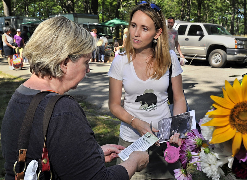Katie Hansberry of the Maine chapter of the Humane Society hands out pamphlets at the farmers market in Portland's Deering Oaks park Saturday. Animal-welfare advocates want to ban three bear-hunting methods: baiting; using dogs; and using snare traps.