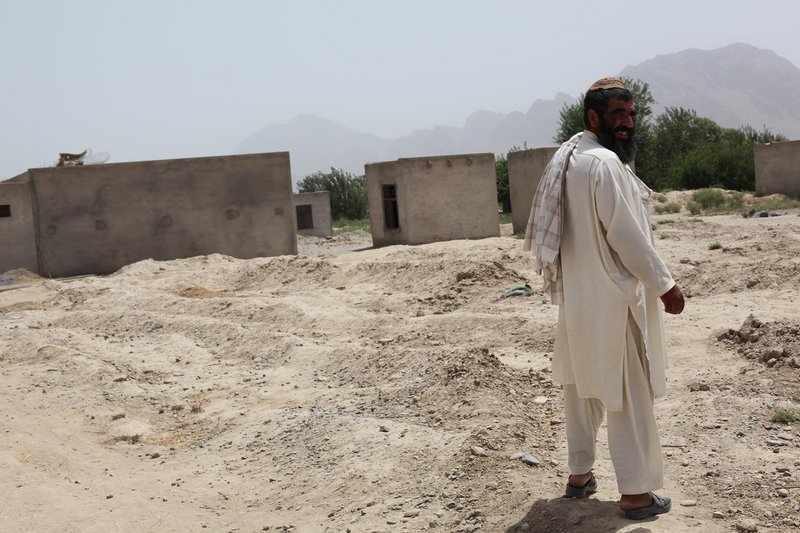 Niaz Mohammad stands on the land that was covered by Tarok Kolache's houses before Americans bombed the village in 2010. Less than half of the village was rebuilt after the bombardment.