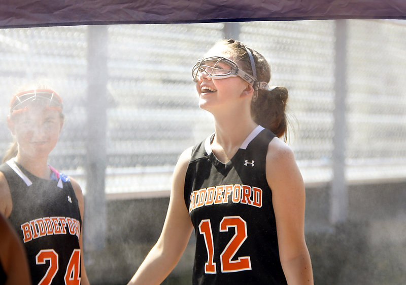Biddeford's Charlotte White cools off at a misting tent after the Tigers' scrimmage against South Portland on Tuesday.