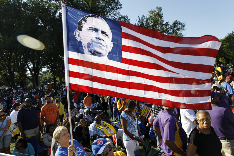 """Dorothy Meekins holds up a flag with a picture of President Obama as she attends the rally in Washington on Saturday commemorating the 50th anniversary of the 1963 March on Washington. In an interview Tuesday, Obama said he imagined King """"would be amazed in many ways about the progress we've made."""""""