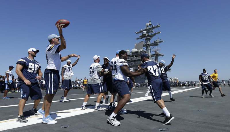 Chargers quarterback Philip Rivers, second from left, throws a pass during a lighthearted workout on the flight deck of the USS Ronald Reagan aircraft carrier on Wednesday. The Chargers play their final preseason game on Thursday against the San Francisco 49ers.