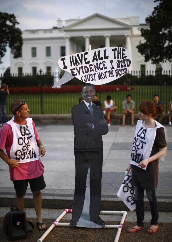 Protesters against U.S. military intervention in Syria stand beside a cutout of President Obama at a rally Thursday outside the White House. Skeptics want solid evidence linking the Assad regime to the use of chemical weapons.