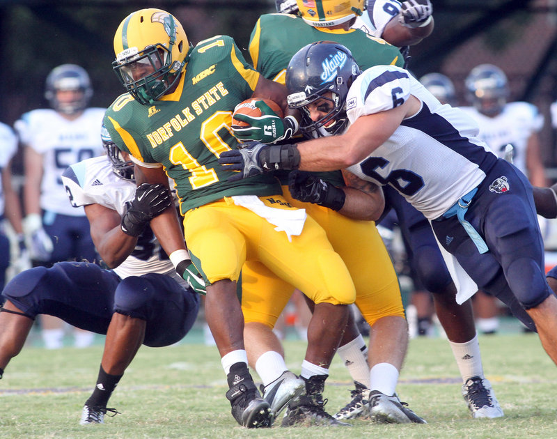 Maine linebacker Troy Eastman, right, stops Norfolk State running back Brendon Riddick short of a first down in the first half Saturday at Norfolk, Va. Maine held the Spartans to 227 yards in a 23-6 win.