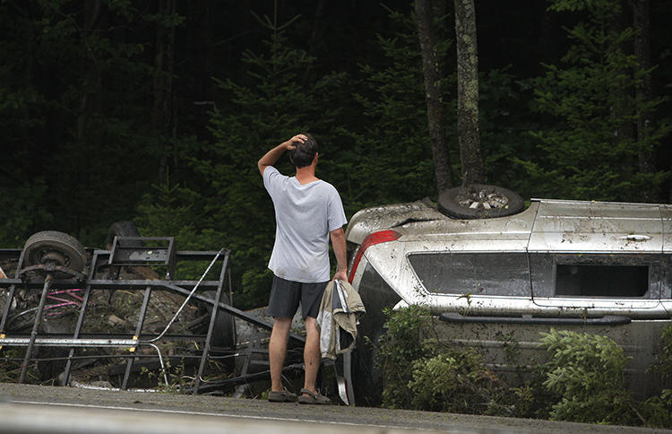 A man surveys the damage to a vehicle that crashed on Interstate 295 at mile 25 northbound in Freeport on Friday.