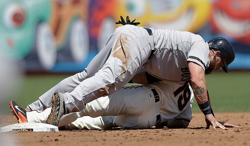Boston's Jonny Gomes lies on top of Giants second baseman Marco Scutaro after being tagged out during third-inning action of Wednesday afternoon's game in San Francisco, won convincingly by the Red Sox. AT&T Park