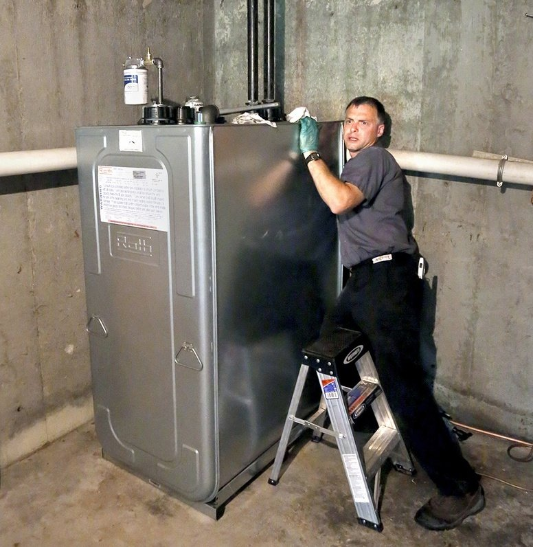 Chris Sprague, a service manager at Giroux Energy, installs a 275-gallon Roth oil tank recently in a Gorham home. The unit has an outer jacket that is meant to contain potential spills.