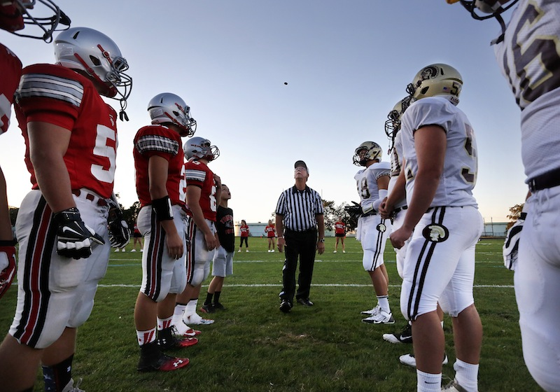 Captains from South Portland and Thorton Academy watch as referee Bob Webb tosses the coin to decide first possession on Friday, September 6, 2013.