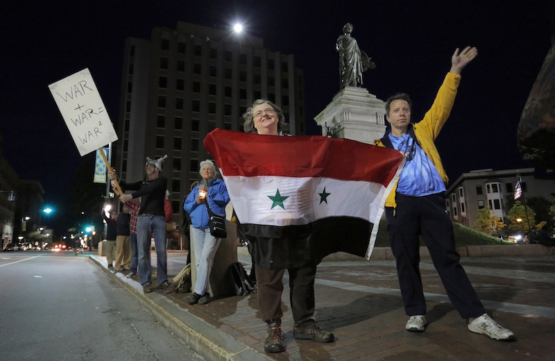 Lucinda McGinn, of Westbrook, and her husband Peter McGinn, hold a Syrian Flag and wave to passing traffic as part of a gathering in Monument Square on Monday evening, September 9, 2013, to protest the proposed military action in Syria by the United States.