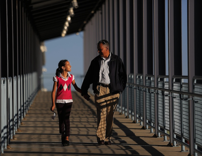 With the American flag in one hand and her father's hand in the other, Charlotte Urquhart of Bangor, left, walks out of Ocean Gateway with her dad Benjamin Urquhart, after Benjamin's wife and Charlotte's mother, Christine Urquhart, originally from France, became a U.S. Citizen at a Naturalization Ceremony on Tuesday, September 17, 2013.