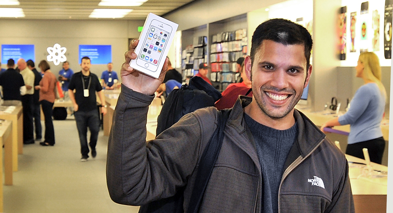 Matthew Baker of Portland is the first to leave the Apple Store at the Maine Mall on Friday with a gold iPhone 5s.