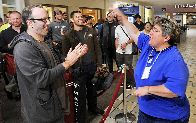 Apple Store leader Pam Famous greets Dan Kennedy of South Portland, who had waited since 3 a.m. Friday for a chance to buy a gold iPhone 5s.