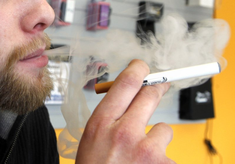 A sales associate demonstrates the use of an electronic cigarette, which emits smokelike vapor, in Aurora, Colo.
