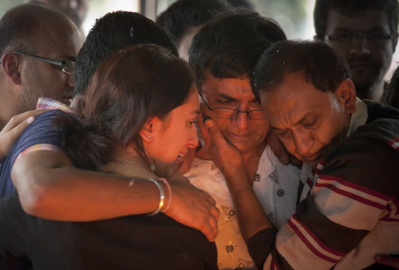 Ramesh Vaya, center, is comforted by family members after lighting the funeral pyre for his wife Malti, who was shot dead in the attack on the Westgate Mall, at her funeral at the Hindu Crematorium in Nairobi, Kenya Tuesday, Sept. 24, 2013. Ramesh and his brother both lost their wives in the attack. Kenyan President Uhuru Kenyatta says security forces have finally defeated a small group of terrorists after four days of fighting at the Nairobi mall.