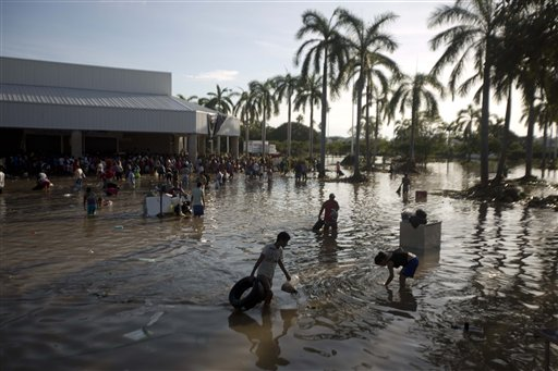 People wade through waist-high water in a store's parking, looking for valuables, south of Acapulco, in Punta Diamante, Mexico, on Wednesday. Mexico was hit by the one-two punch of twin storms over the weekend, and the storm that soaked Acapulco on Sunday – Manuel – re-formed into a tropical storm Wednesday, threatening to bring more flooding to the country's northern coast.