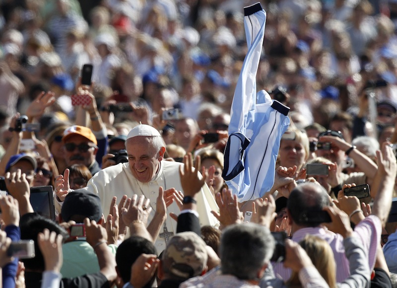 A faithful tosses in the air a jersey with the colors of the Argentine flag as Pope Francis greets faithful upon arrival for his weekly general audience in St. Peter's Square at the Vatican, Wednesday, Sept. 18, 2013. (AP Photo/Riccardo De Luca)