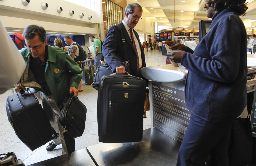 Passengers check their luggage at the Delta counter at Hartsfield-Jackson Atlanta International Airport, in Atlanta last week. Delta customers have the new option to purchase an upgrade that includes a second bag to check, among other perks.