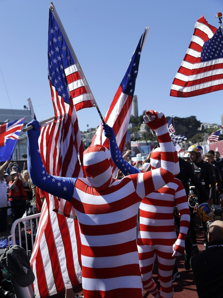 Oracle Team USA fans cheer during a dockout show prior to the 19th race of the America's Cup sailing event against Emirates Team New Zealand Wednesday, Sept. 25, 2013, in San Francisco.