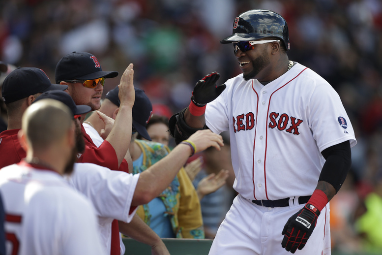 Boston Red Sox's David Ortiz, right, is welcomed to the dugout after hitting a home run in Sunday's game at Fenway Park in Boston. The Red Sox are headed to their first postseason in four years.