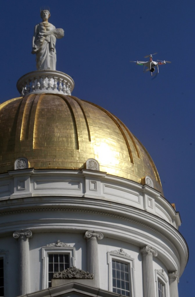 A drone is flown over the Statehouse in a demonstration by the Vermont chapter of the American Civil Liberties Union on Tuesday, Sept. 17, 2013 in Montpelier, Vt. Executive director Allen Gilbert says the ACLU is going to ask the Legislature to regulate surveillance of private citizens by state, local and federal law enforcement agencies. (AP Photo/Toby Talbot)