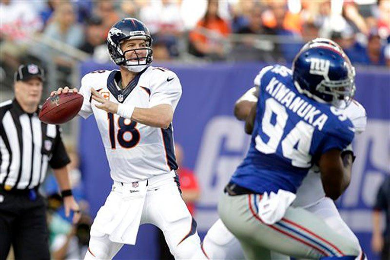 Denver Broncos quarterback Peyton Manning (18) throws a pass during the first half against the New York Giants Sunday in East Rutherford, N.J.